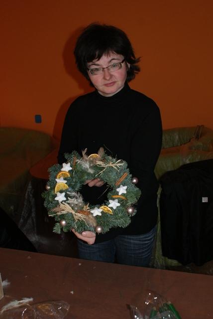 Uczestniczka Projektu prezentuje swój wieniec bożonarodzeniowy.