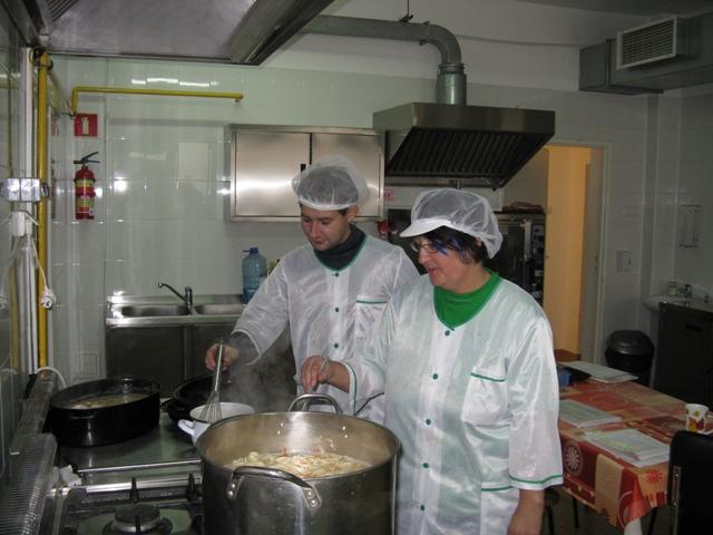 dwoje uczestników gotujących zupę